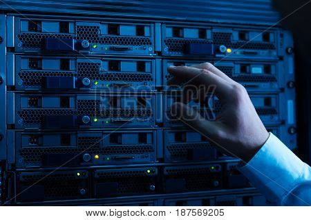 Network server. Close up of a hand of a professional experienced engineer pressing the button on the network server