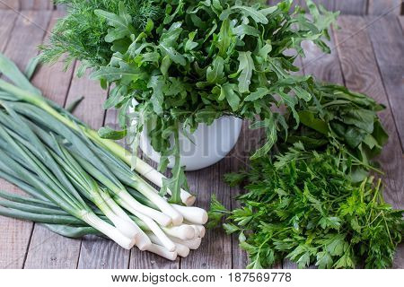 Fresh garden herbs over wooden table. Green: green onions dill and basil.