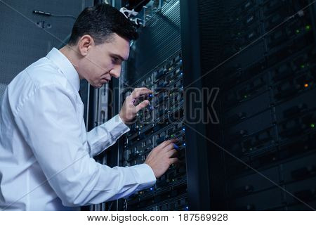 Data storage. Nice professional male engineer standing near the network server and checking it while working in the data server