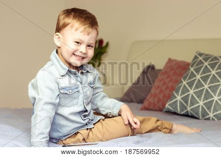 Little Cute Boy Plays On The Bed. Boy 3 Years Sitting On The Bed. Little Happy Boy. Toned Photo.