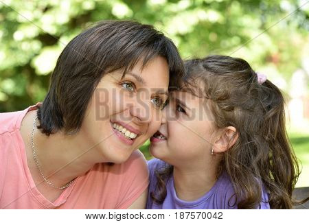 Daughter whispering secret into ears of smiling mother