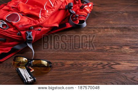 Set for travel: orange tourist backpack, sunglasses and gear for the bicycle on the wooden background. Horizontal photo of the travel accessories set. Planning and preparation for the trip. Concept of the active lifestyle.