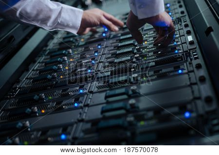 Storage of data. Close up of a network server standing in the data center and being checked by a nice professional male programmer