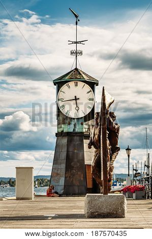 Oslo, Norway - July 31, 2014: Big Clock And Steeple Of Old Lighthouse At Aker Brygge District. Dramatic Blue Cloudy Sky Background