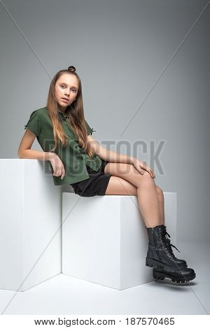 Young beautiful girl sitting on cube. woman dressed in green T-shirt, black shorts and large army boots. Shoot in studio