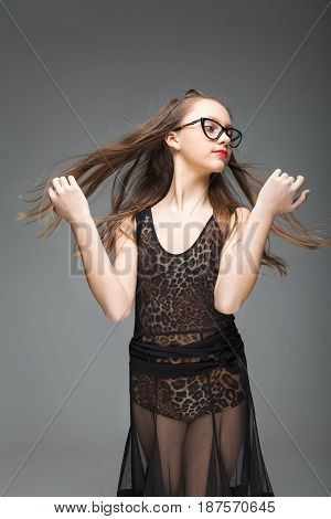 young girl in stylish glasses throws up his long hair. She is dressed in a black dance dress with a leopard pattern