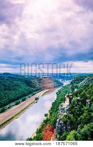 View from the Bastei to the river Elbe in Saxon Switzerland. Sun flares coming through the clouds. Dresden. Germany.