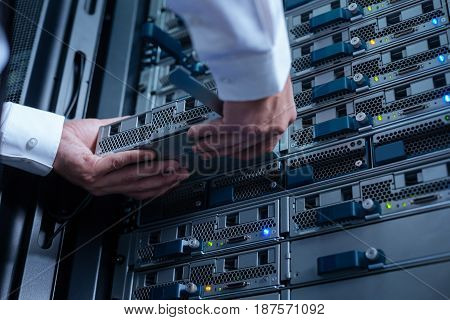 Collecting data. Close up of a blade server being held by a professional experienced engineer while putting in into server rack