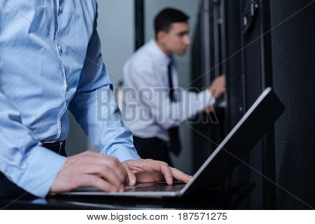Entering data. Nice pleasant adult man standing near the laptop and typing on it while working with his colleague in the data center