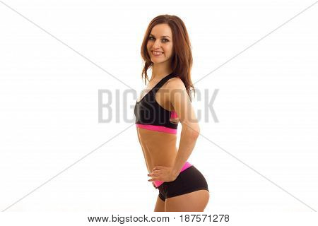 young sexy gymnast shorts stands sideways in front of the camera and smiling isolated on white background