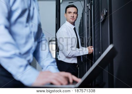 Working together. Positive pleasant handsome man standing near the server rack and looking at his colleague while working together with him