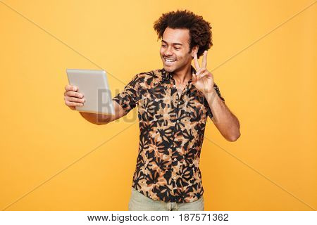 Portrait of a happy young african man holding pc tablet and showing peace gesture isolated over yellow background