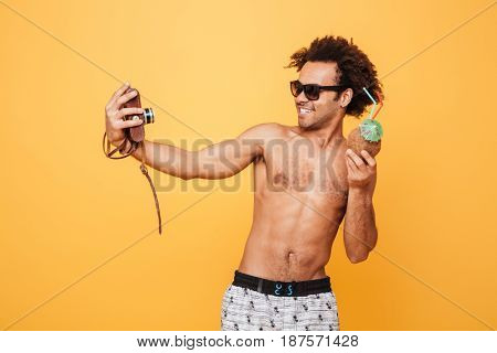 Picture of happy young african man dressed in shorts standing isolated over yellow background. Looking aside while make selfie and drinking cocktail.