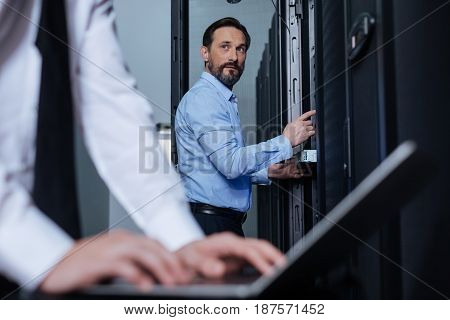 Professional engineers. Handsome nice bearded man looking at his colleague and pressing a button on the data server while working in the server room