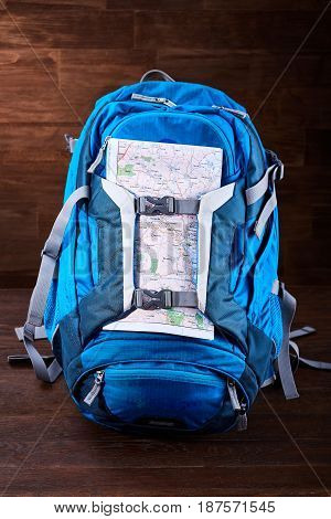 Tourist blue big backpack and map against wooden background. Equipment for the travelling. Tourist backgrounds and still-life. Planning and preparation for the travelling. Trip around the world. Concept of the active lifestyle.