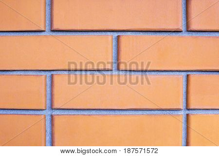Brick wall close-up of orange bricks with smooth cement-sand seam