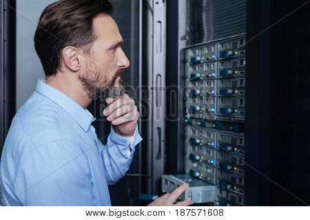 Where is it. Thoughtful serious nice man standing in front the server rack and looking for a problem while checking it