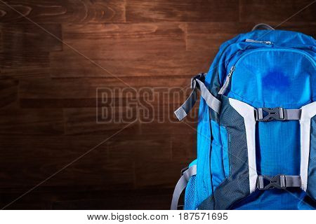 Tourist blue backpack against wooden background. Horizontal photo of the bright rucksack. Planning and preparation for the travelling. Trip around the world. Travelling backgrounds and still-life. Concept of the active lifestyle.