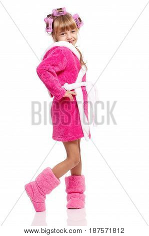 Portrait of pretty little girl in pink bathrobe with curlers on her head isolated on white background