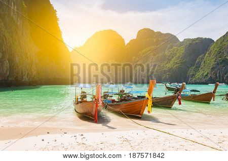 Traditional long tail boats docking in Maya bay in front of a clear and sandy beach in Krabi nearby Phuket island Thailand; light filtered