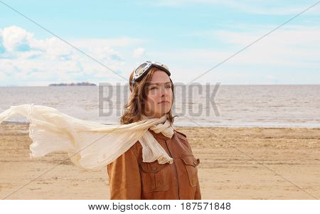 A Beautiful Young Girl Stands On The Shore Of The Bay In The Pilot's Clothing With A Scarf Flying In