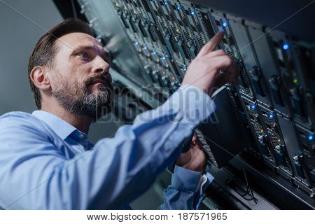 IT administrator. Handsome nice bearded man standing near the rack servers and checking them while working as IT administrator
