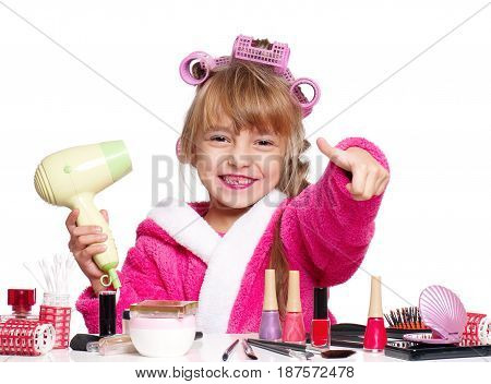 Portrait of pretty little girl seating at table with hairdryer and makeup accessories, on white background