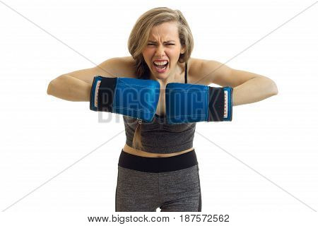 young beautiful blonde standing in front of a camera screams and holds hands in boxing gloves close-up isolated on white background