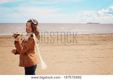 A Girl In A Pilot's Clothes Looks At A Toy Airplane In Her Hand, A Return To Her Childhood, A Copy S