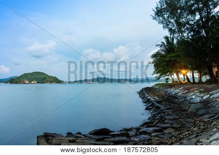 Stone path with lights leading into the sea. Cloudy sky and some small islands are also visible. Perfect vacation spot