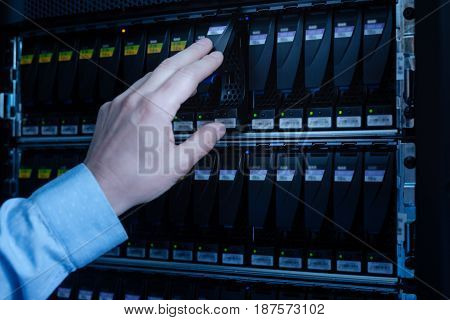 Saving information. Serious professional IT administrator holding the hard drive and examining it while standing near the network server