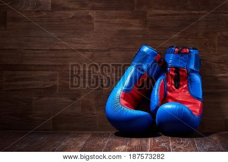 Boxing background with two gloves on the brown plank background. Horizontal photo of the blue and red boxing gloves against wooden wall. Boxing training and exercise. Concept of the sportive lifestyle.