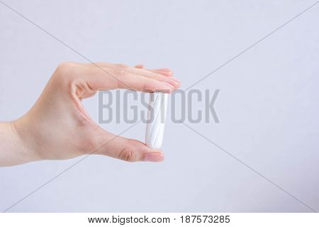 Woman's hand holding clean cotton tampon close-up. Young woman preparing menstruation time. Soft tender protection woman critical days gynecological. Medical hygiene conception