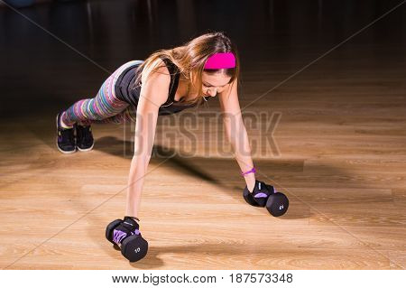 Strong young woman doing push ups exercise with dumbbells. Fitness model doing intense training in the gym