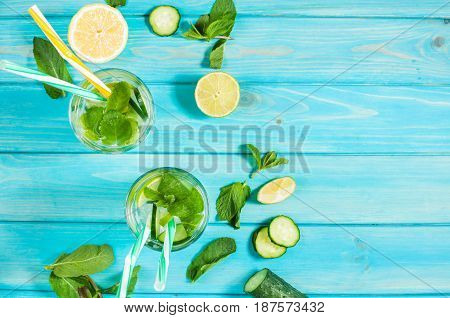 Cold and refreshing infused detox water with lime mint and cucumber in a glass on wood background. Top view and copyspace