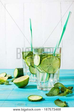 Cold and refreshing infused detox water with lime mint and cucumber in a glass on wood background.