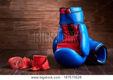 Pair of red and blue boxing gloves and red bandage on brown plank. Horizontal photo of colorful boxing accessories against wooden background. Boxing backgrounds and still-life. Concept of the sportive lifestyle.