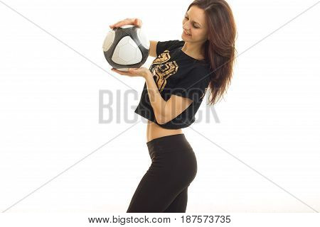 athletic young girl stands sideways smiles and holding a soccer ball isolated on white background