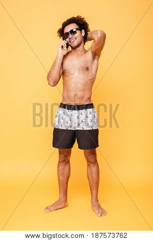 Image of happy young african man dressed in shorts standing isolated over yellow background. Looking aside while talking by mobile phone.