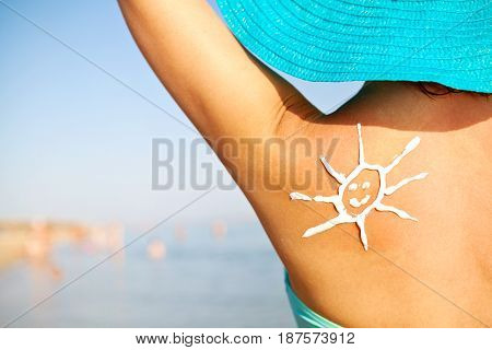 Picture of sun sunscreen on shoulder of young girl in blue hat on beach