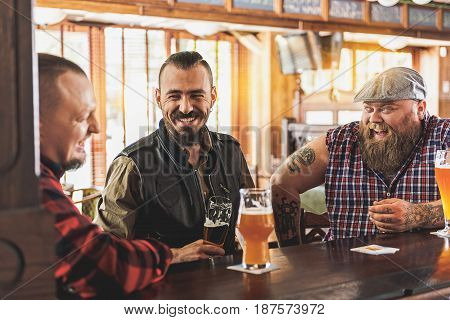Involved in discussion. Cheerful positive bearded men drinking beer and communicating with each other while sitting at bar counter. They enjoying ale after work