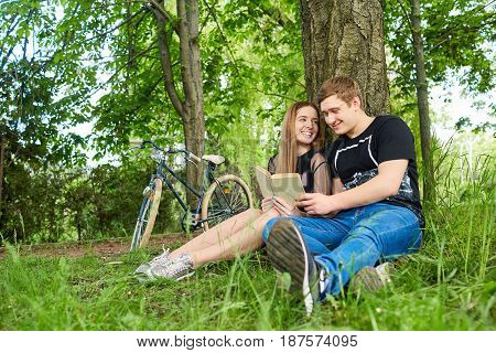 Happy couple of students are reading a book in the park.