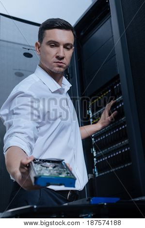 Keeping data. Serious good looking male technician holding a hard drive and intending to put it into server rack while working with the network server