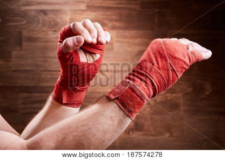 Close-up of the muscular man's hands with red bandage against wooden wall. Horizontal photo and brown background. Boxing exercise and training. Boxing backgrounds. Energy, power and victory. Concept of the sportive lifestyle.
