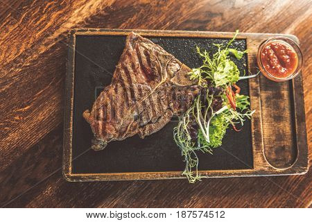 Meal of real man. Top View Close Up of appetizing grilled T-bone steak with fresh salad and spicy sauce. Wooden table in the background