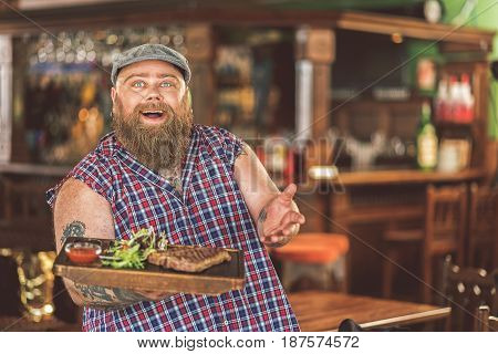 Bon appetite. Waist-up portrait of cheerful bearded man standing with wooden tray while gesturing positively. He looking at camera with joy