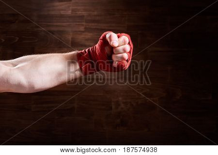 Boxer fist punch with red bandage on a wooden background. Horizontal photo and brown wall. Boxing equipment and backgrounds. Sportive exercise and training. Concept of the sportive lifestyle.