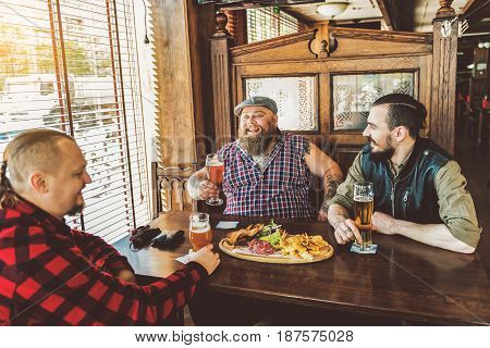 Close friendship. Positive fat man sharing news with his friends. They sitting in pub drinking beer and laughing