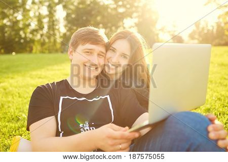 A loving couple with  laptop in the park at sunset.