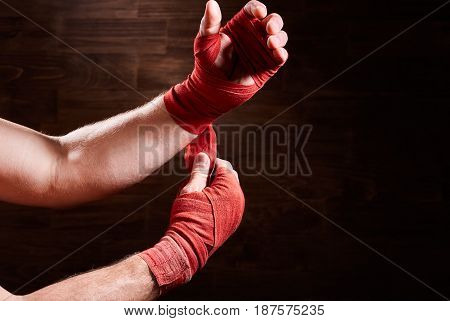 Boxer putting bandage around wrists and hands against brown wall. Horizontal photo and wooden background. Boxing equipment and backgrounds. Energy, power and victory. Concept of the sportive lifestyle.
